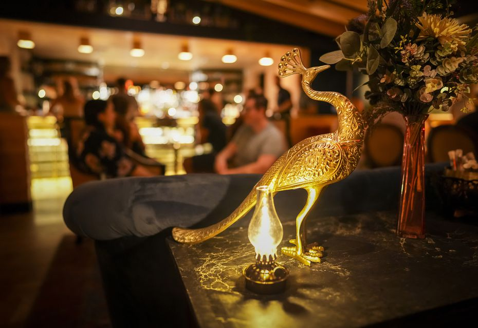 The cocktail den Apothecary is decorated in antique golds and fun wallpaper.