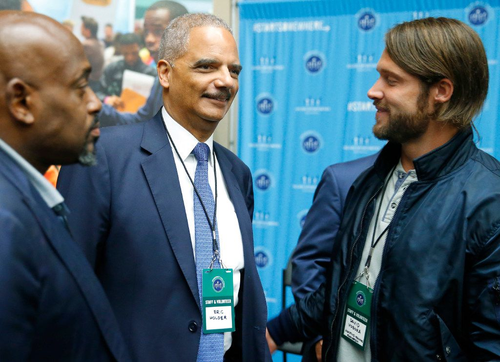 Former Attorney General Eric Holder (center) visits with David Vobora (right) of Adaptive Training Foundation during a visit to the 100K Opportunities Fair at the Kay Bailey Hutchison Convention Center in Dallas, Friday, May 19, 2017. (Tom Fox/The Dallas Morning News)