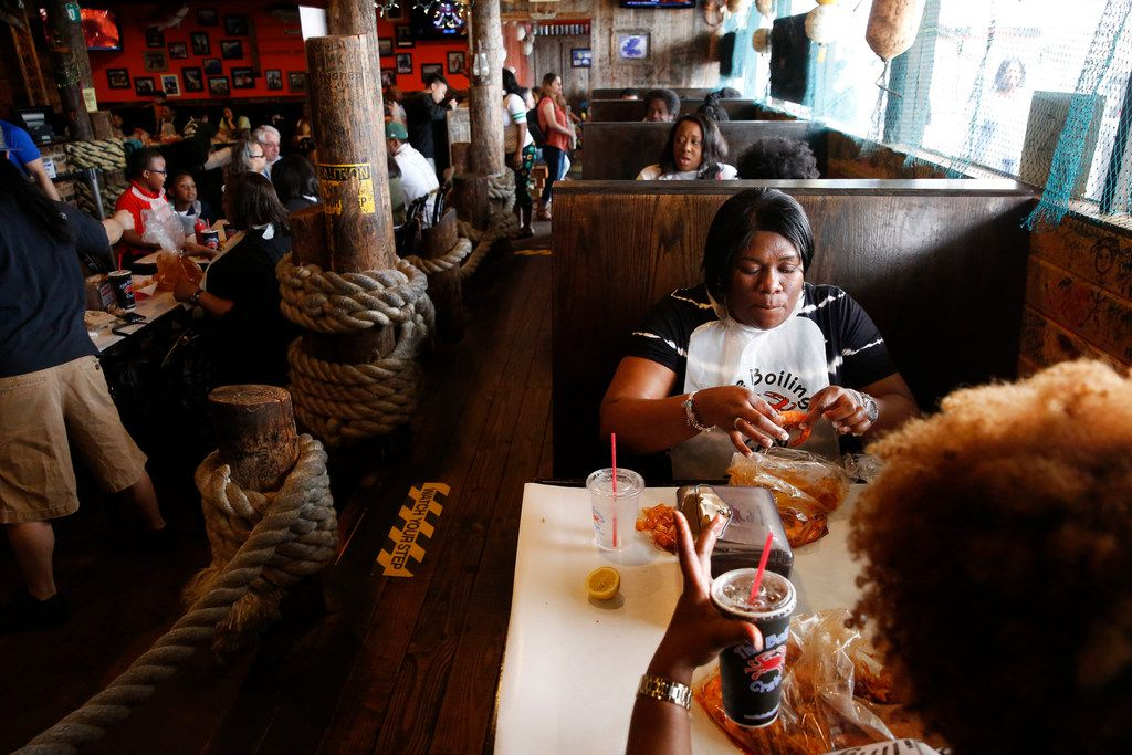 Anissa Collins-Fortune (top) eats shrimp in a booth with her friend Tamieka Stringer at The Boiling Crab in Dallas.