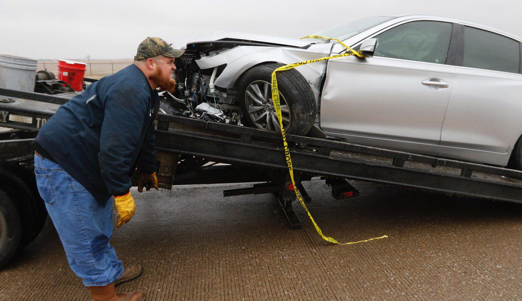 David Messer of J & S Towing hooks up a wrecked car on an ice-covered Highway 67/Hampton Road overpass in Dallas on Sunday afternoon, Dec. 31, 2017. Dallas Fire-Rescue Department was waiting for sand trucks.
