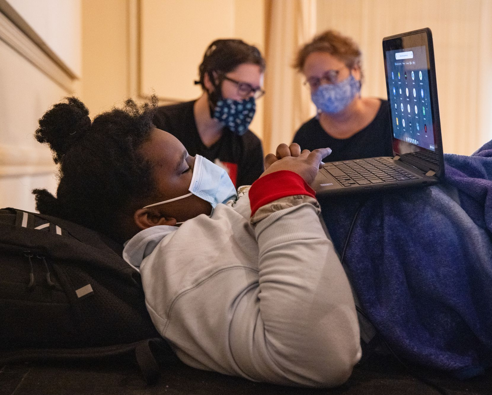 (From left) Madison Lewis, 10, uses a laptop as Thomas Stuteville and Karen Arnold chat as they seek refuge at the warming center located at Ruthe Jackson Center in Grand Prairie on Tuesday, Feb. 16, 2021. The family lost power at 12:16pm on Monday. (Juan Figueroa/ The Dallas Morning News)