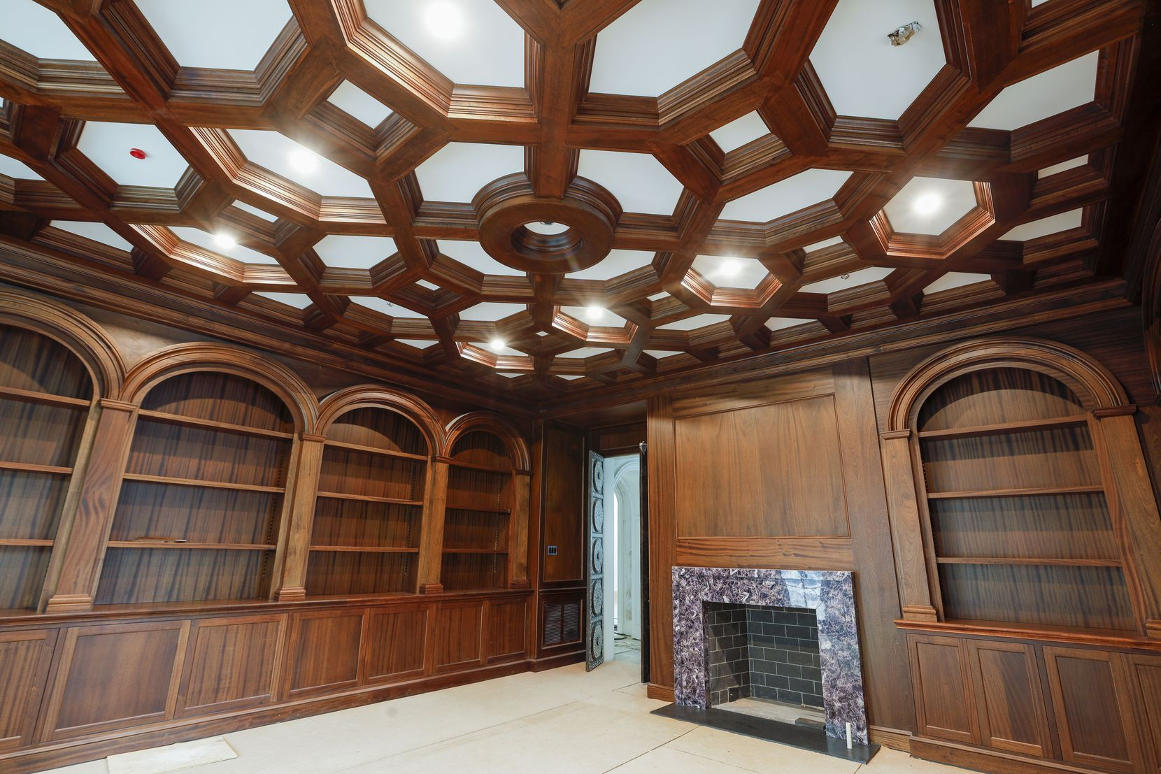 The library at 6915 Baltimore Drive has African mahogany-lined walls and bookshelves and an amethyst fireplace surround.