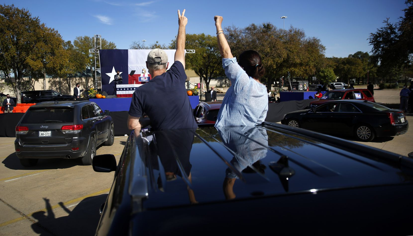 Through the sunroof of their vehicle, Biden campaign staffer Teri Ervin (right) and her husband Tom Ervin of Dallas cheer former second lady Jill Biden who made a drive-in campaign rally speech on behalf of her husband and Democratic Presidential candidate Joe Biden, at Fair Park in Dallas, Tuesday, October 13, 2020. It was the first day of early voting in Texas.