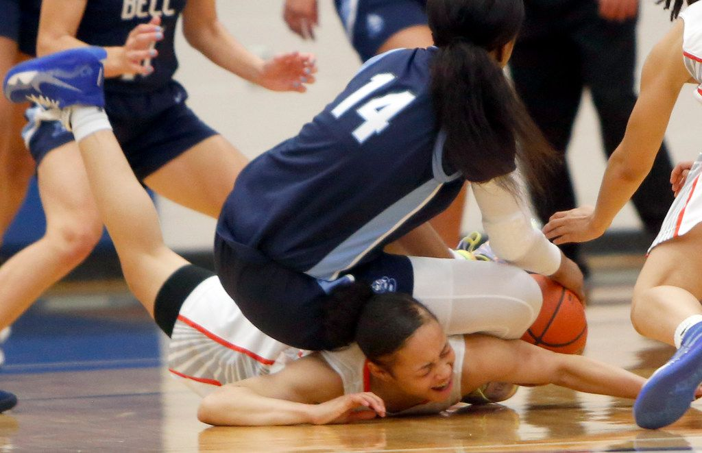 Arlington Bowie guard Alexis Smith (4) winces in pain as she tumbles with Hurst L.D. Bell guard Kyla Davis (14) as the two battled for a loose ball during first half action. The two teams played their Class 6A bi-district girls basketball game at Grand Prairie High in Grand Prairie on February 17, 2020. (Steve Hamm/Special Contributor).
