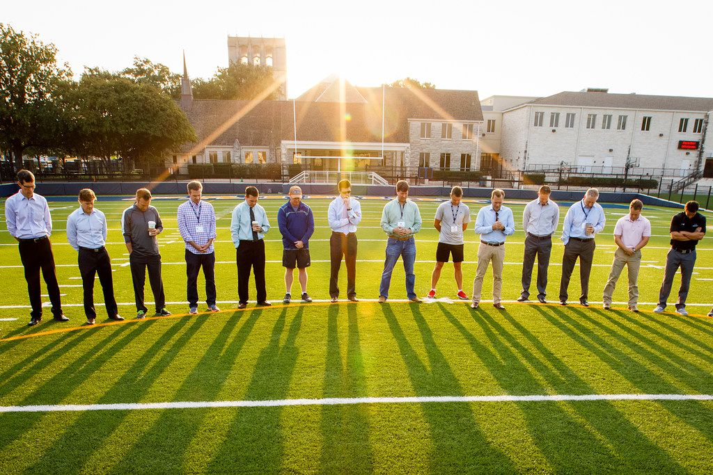 As the sun rises over the school, dads and faculty gather on the athletic field to walk the field and pray for the year at Providence Christian School on Wednesday, Sept. 13, 2017, in Dallas.
