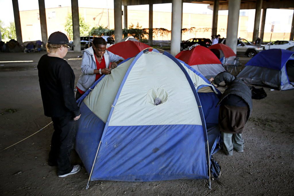 People pitch a tent under I-45 south of downtown after being kicked out Tent City Tuesday, May 3, 2016 in Dallas. The final two sections of the contentious homeless encampment where closed Tuesday morning, sending the remaining residents scrambling for shelter.