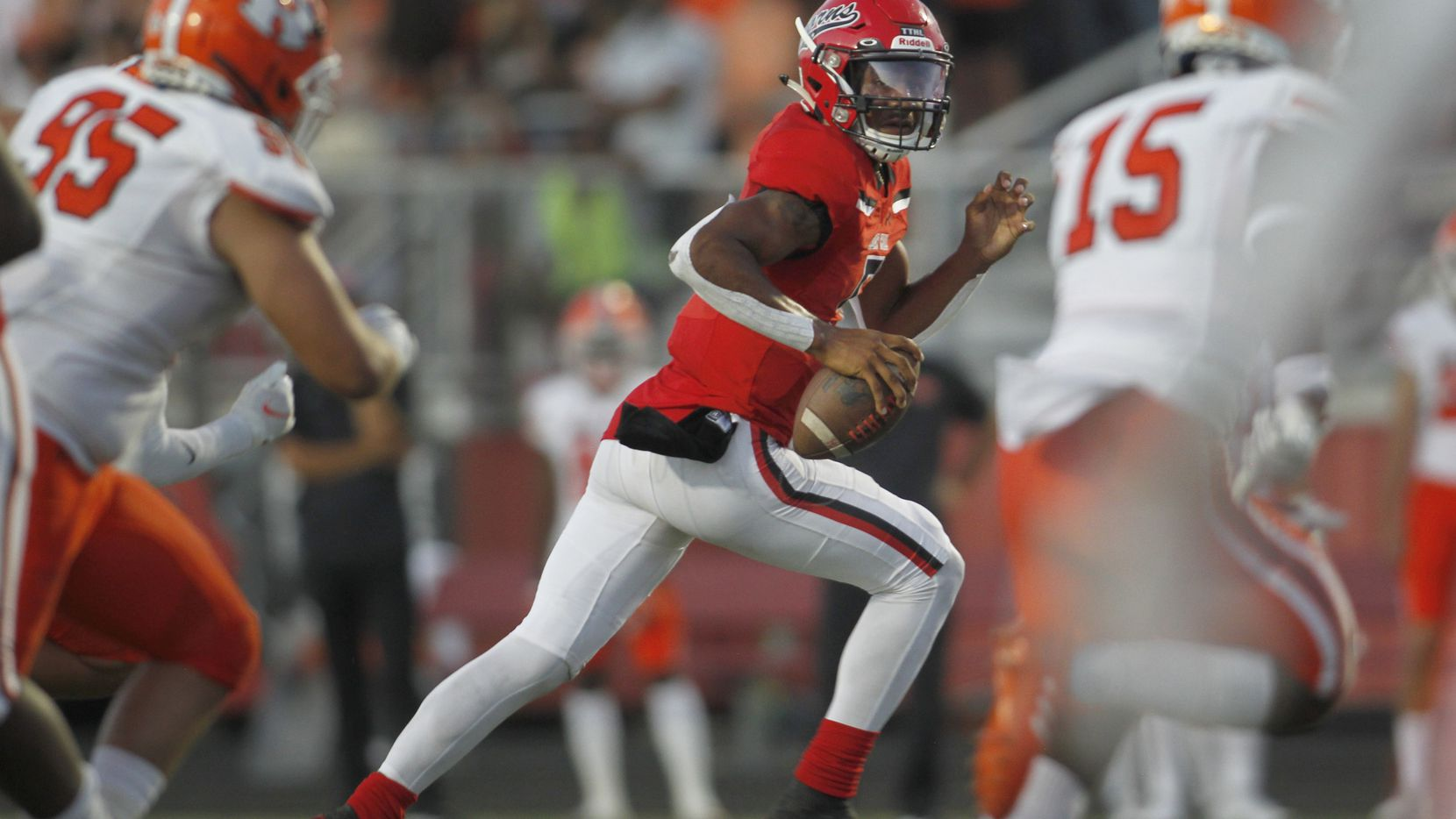 Cedar Hill quarterback Cedric Harden, Jr. (5) rolls out in search of a receiver as Rockwall defenders pursue during first half action. Cedar Hill and Rockwall played their season opening football game at Longhorn Stadium in Cedar Hill on August 27, 2021.
