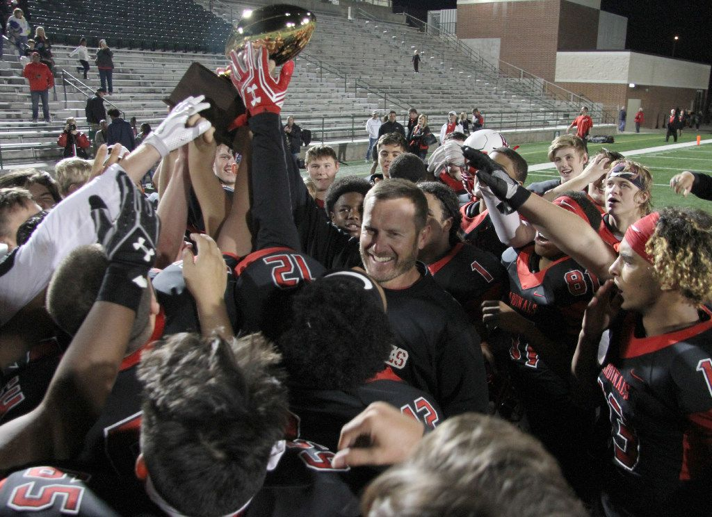Melissa head coach Seth Stinton was all smiles as he raised the bi-district trophy as he celebrated with his players following their victory over Dallas Lincoln.  The two teams played their bi-district round football playoff game at Mesquite Memorial Stadium in Mesquite on November 10, 2016. (Steve Hamm/Special Contributor)