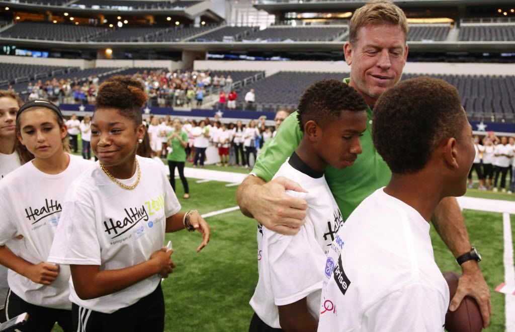 Students from Arlington ISD's Young Junior High School, from left, Rylee Richardson, 13, Cassady Frey,13, Ta'Naya Thurmund,13, K.J. Polk, 13, and Christian Traylor, 13,  wait for  former Dallas Cowboy Troy Aikman to throw them the ball at the expansion celebration of The Healthy Zone School Recognition Program at AT&T Stadium in Arlington in 2015.