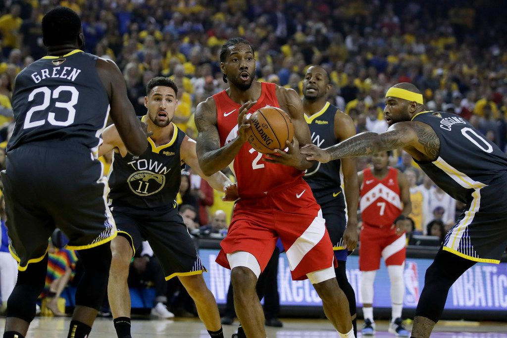 Toronto Raptors forward Kawhi Leonard (2) looks to pass between Golden State Warriors forward Draymond Green (23), guard Klay Thompson (11), forward Andre Iguodala, rear, and center DeMarcus Cousins (0) during the first half of Game 4 of basketball's NBA Finals in Oakland, Calif., Friday, June 7, 2019. (AP Photo/Ben Margot)