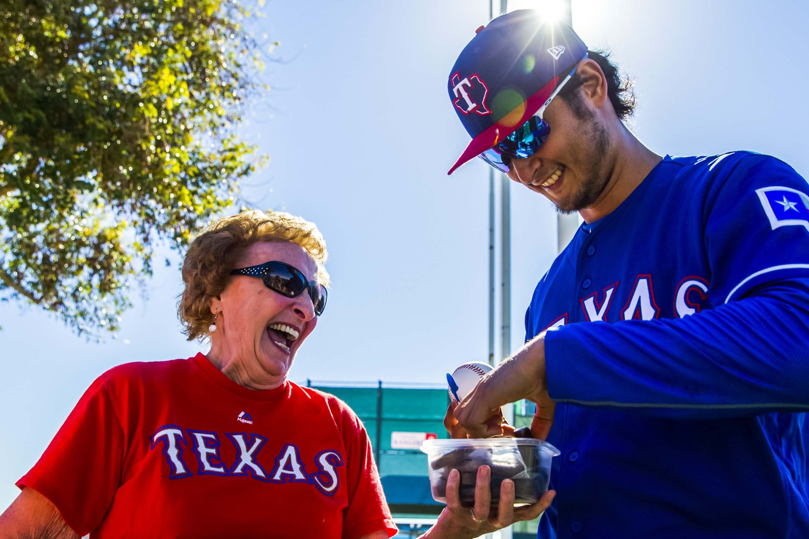 "Shirley Kost, also known as ""the cookie lady,"" gives a cookie to Texas Rangers starting pitcher Yu Darvish (11)  during a spring training workout at the team's training facility on Thursday, February 16, 2017 in Surprise, Arizona. (Ashley Landis/The Dallas Morning News)"