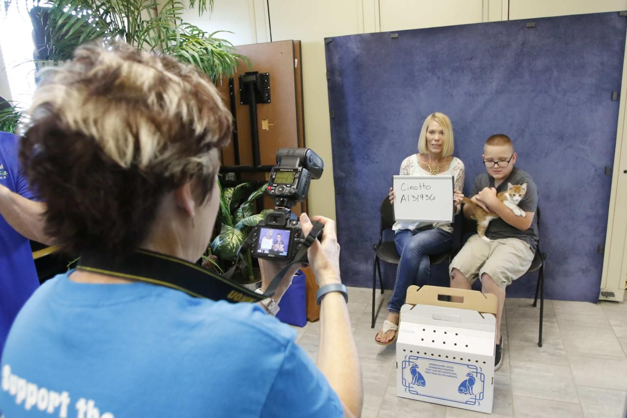 Bethany Cinotto and her son Kylen Kraus have their picture taken with their new cat, Scotch, during the Clear the Shelter event at Prairie Paws Adoption Center in Grand Prairie on Aug. 15.
