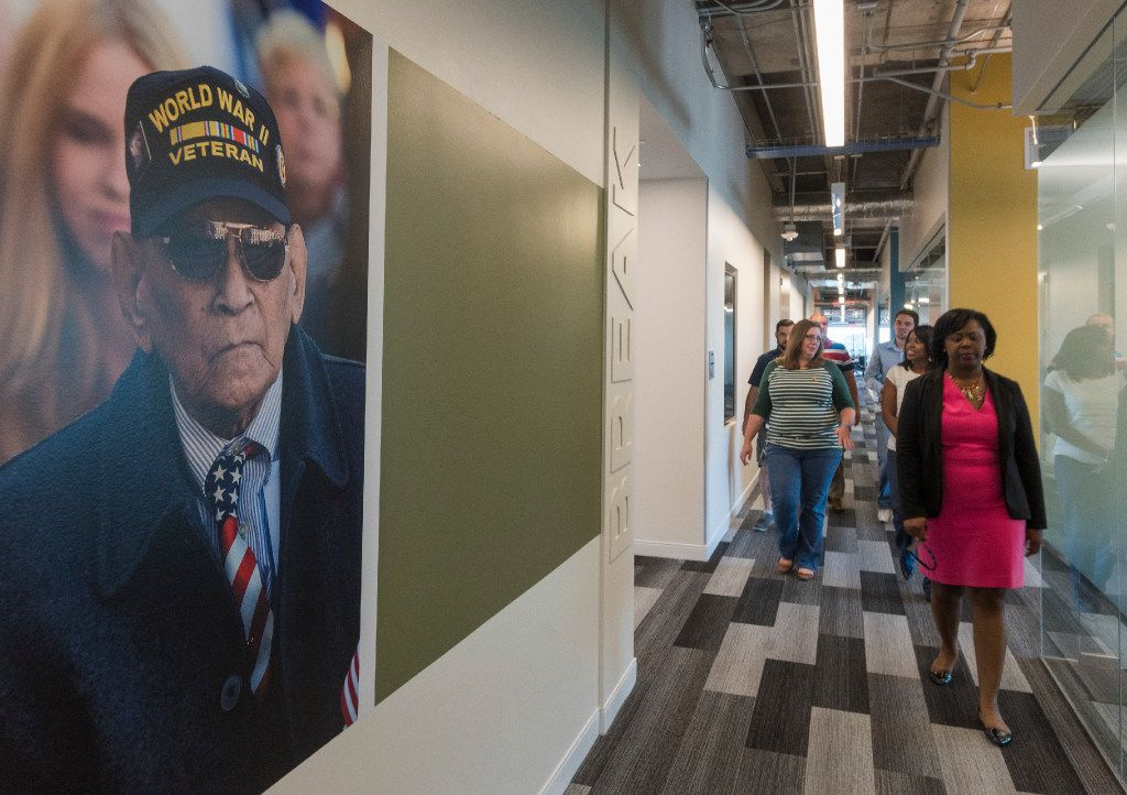 USAA workers walk down the hallway of the insurance company's office building in Plano.