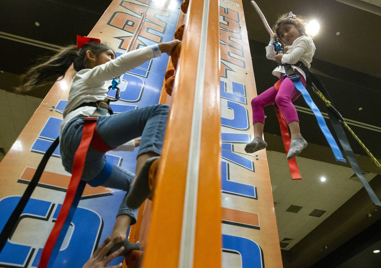 Zanaib Qureshi from Midland, Texas, (right), 4, looks at her sister Jannat, 6, as they climb the rock climbing attraction at the Day 1 Dallas festival held this year at the Embassy Suites Conference Center in Frisco, Texas, on Wednesday, Jan. 1, 2020. Day 1 Dallas is a kid-friendly New Year's Day festival that features rock-climbing, arts and crafts, bounce houses, and a fireworks show.