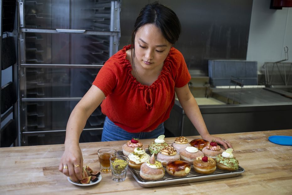Jinny Cho, owner of Detour Doughnuts and Coffee, puts finishing touches on a assorted doughnuts at Detour Doughnuts and Coffee in Frisco in 2019. Park is a second generation Korean-American.