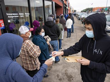 Volunteer Favian Hernandez (right) hands out numbers to the 187 person waiting in line for a COVID-19 vaccine registration site outside of Jerry's Supermarket on West Jefferson Boulevard in Dallas on Friday, Jan. 22, 2021. (Juan Figueroa/ The Dallas Morning News)