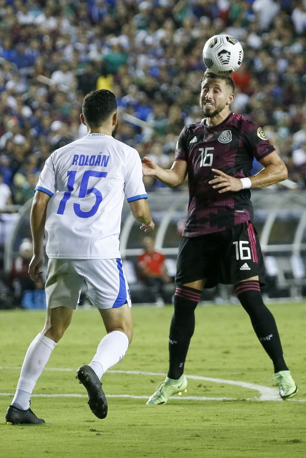 Mexico midfielder Héctor Herrera (16) heads the ball away from El Salvador midfielder Alexander Roldan (15) during the second half of a CONCACAF Gold Cup Group A soccer match at the Cotton Bowl on Sunday, July 18, 2021, in Dallas. (Elias Valverde II/The Dallas Morning News)