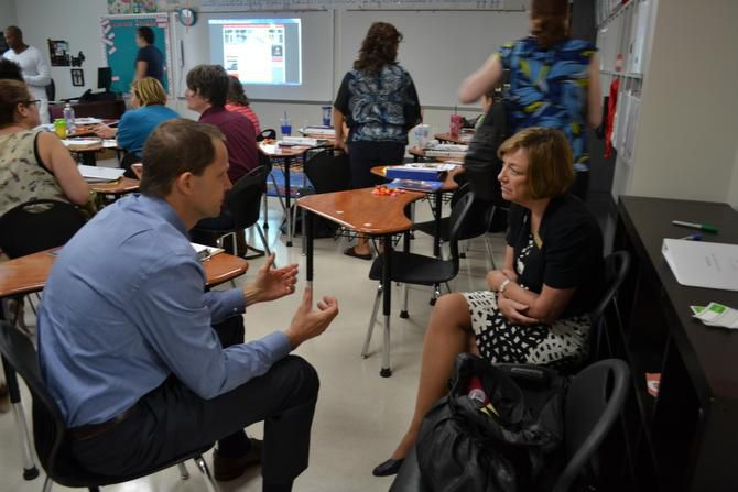Don Menzies, assistant head of school and director of the International Baccalaureate Diploma Years Programme, talks with Nancy Hall, chief academic officer for Imagine Schools, at new teacher orientation  on Aug. 11 at Imagine International Academy of North Texas. The school  has an enrollment of 1,119.