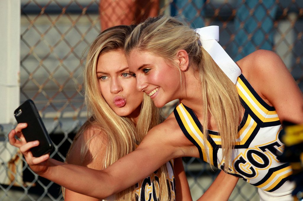 Highland Park cheerleaders Delaney McBee, left, and Annabelle Miller, right, take a selfie together before the start of the team's football game with Rockwall high at Wilkerson-Sanders Stadium in Rockwall on Friday, August 30, 2019. (John F. Rhodes / Special Contributor)