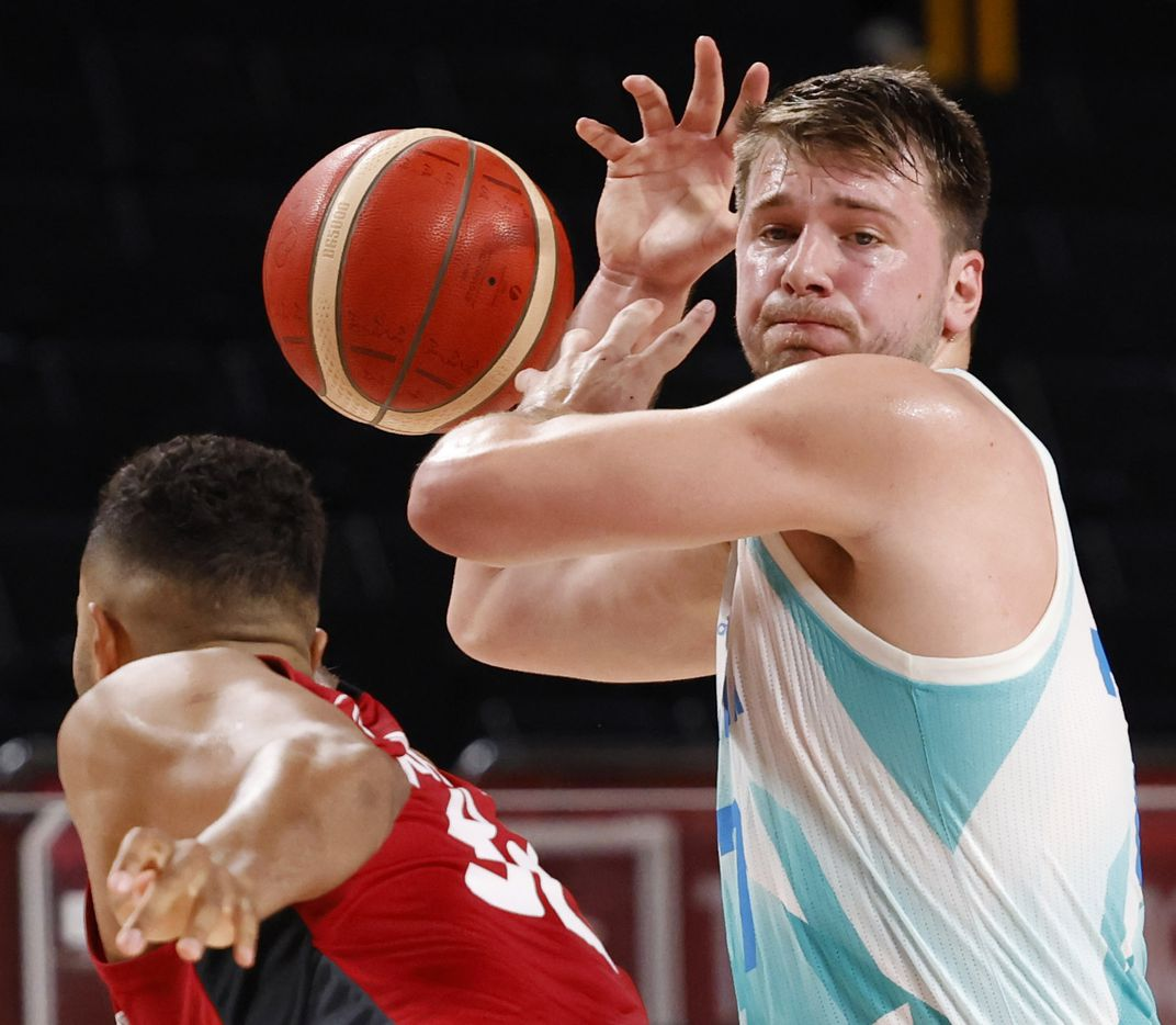 Slovenia's Luka Doncic (77) gets the ball knocked away by Germany's Johannes Thiemann (32) during the first half of play of a quarter final basketball game at the postponed 2020 Tokyo Olympics at Saitama Super Arena, on Tuesday, August 3, 2021, in Saitama, Japan. (Vernon Bryant/The Dallas Morning News)