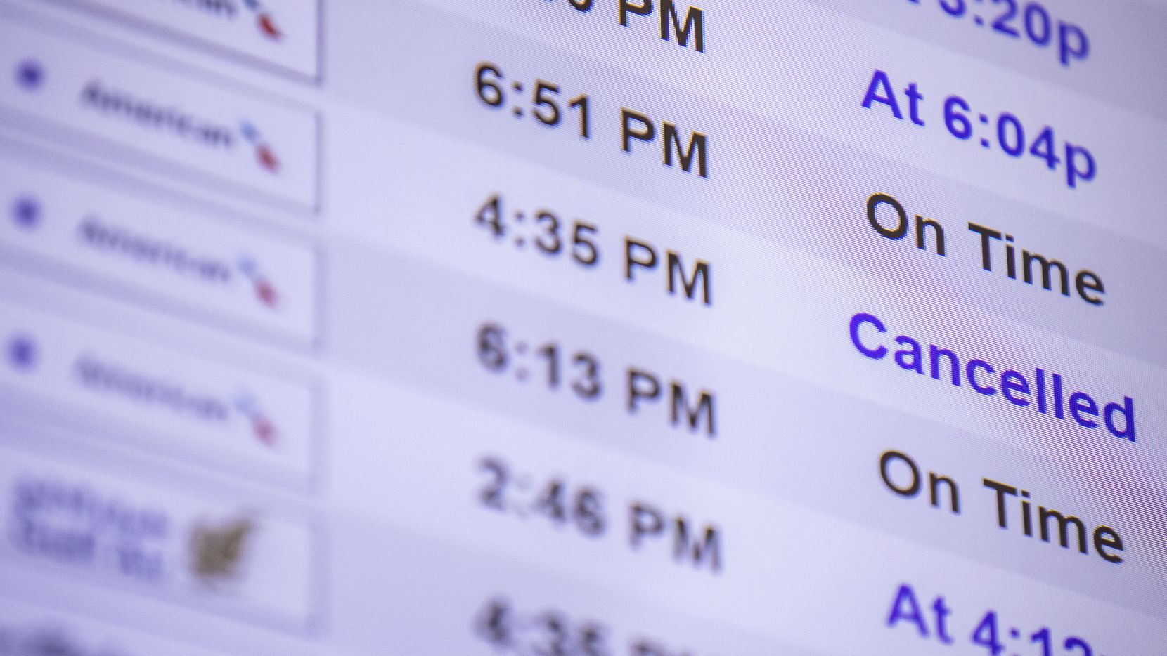 A screen shows a cancelled American Airlines flight in Terminal A of DFW Airport on Monday, July 21, 2021.