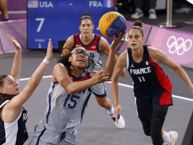 USA's Allisha Gray (15) attempts a shot in front of France's Marie-Eve Paget (5) during a 3x3 women's basketball game during the postponed 2020 Tokyo Olympics at Aomi Urban Sports Park on Saturday, July 24, 2021, in Tokyo, Japan. USA defeated France 17-10 in the game.