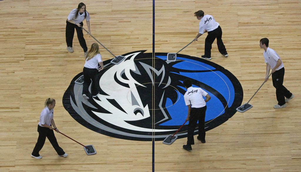 FILE - The Mavs logo at half court gets some TLC during a timeout in a game between the Mavericks and Orlando Magic at American Airlines Center in Dallas on Tuesday, Jan. 9, 2018.