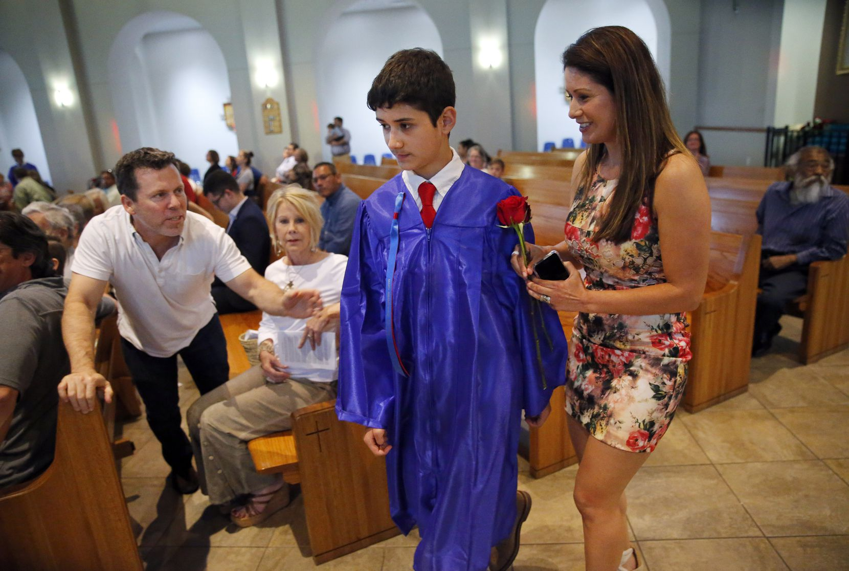 Zack Thibodeaux honored his mother Johanna Uek with a rose as his step-father Joey Uek (left) leans in to congratulate him on his 8th grade graduation.