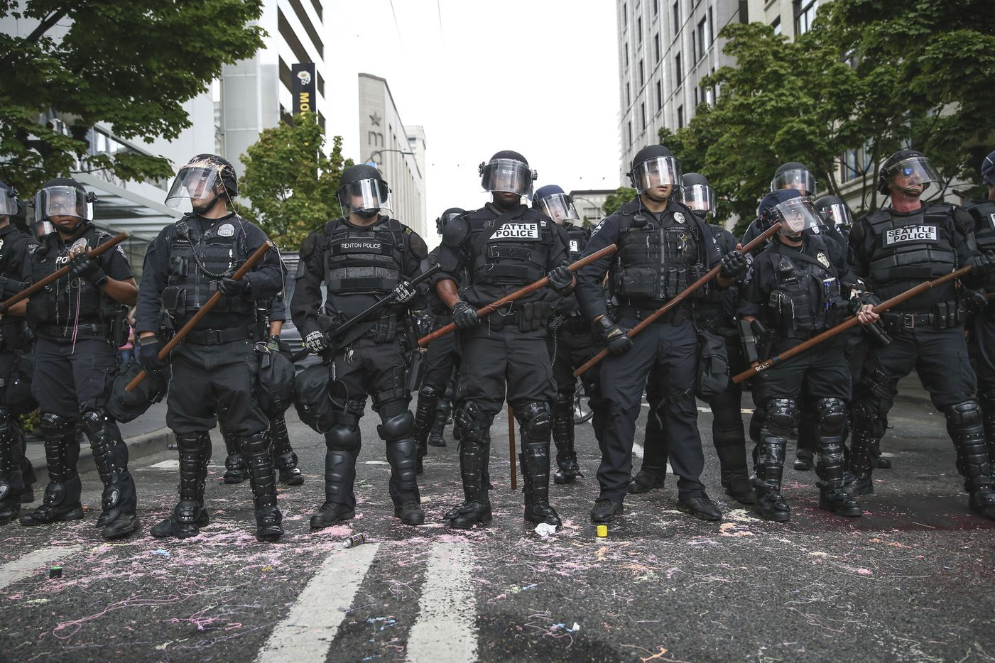Police stand during a rally Sunday, Aug. 13, 2017, in Seattle. Hundreds of demonstrators and counter-protesters converged in downtown Seattle one day after violent clashes in Charlottesville, Va.