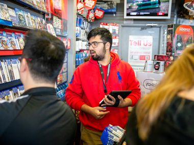 Hamza Khan suggests games for a costumer during Black Friday shopping at GameStop in Fairview, Texas on Thursday, November 22, 2018. (Shaban Athuman/The Dallas Morning News)