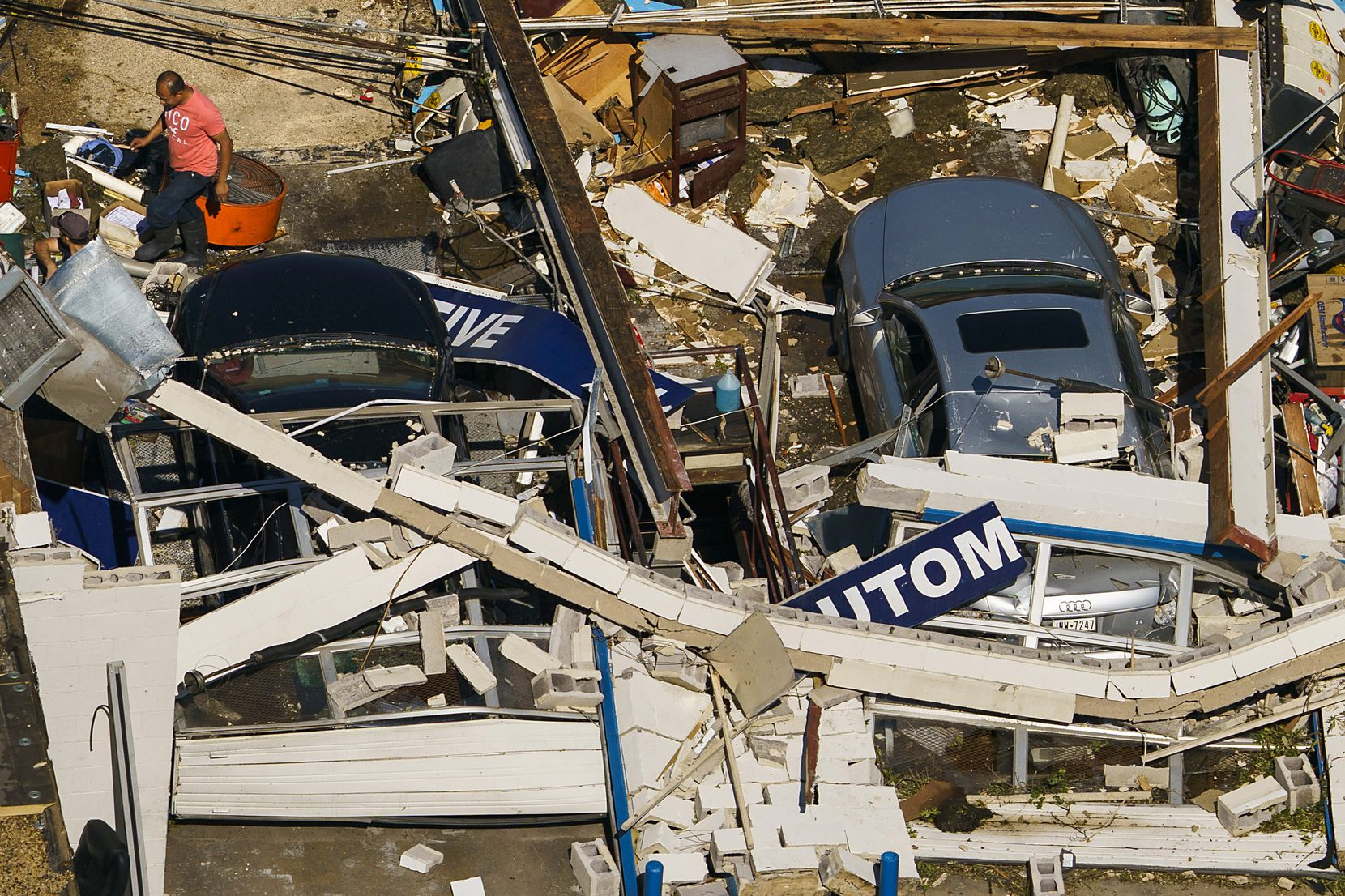 People walk amidst cars buried in the rubble of a destroyed auto repair shop on Northaven Road on Monday, Oct. 21, 2019, in Dallas.