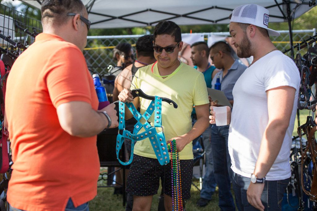 Alvin Alarcon (center) of Dallas inspects a harness during the Texas Latino Gay Pride festival.