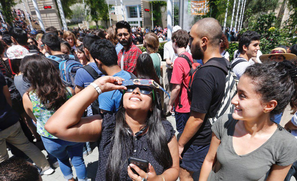 UT Dallas grad students Samragni Dutta Roy, left, and Masih Tajik take turns viewing the solar eclipse with a pair solar eclipse glasses at the schools eclipse watching party in August. (Ron Baselice/The Dallas Morning News)