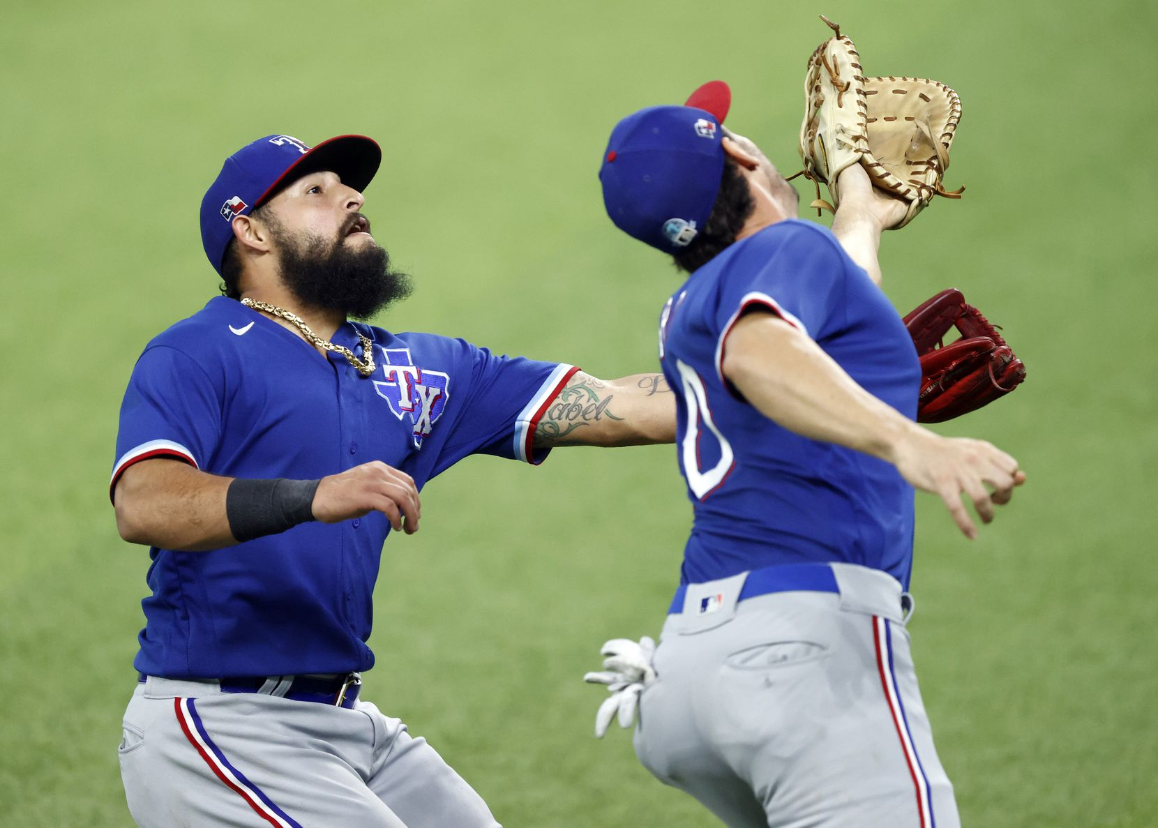 Texas Rangers second baseman Rougned Odor (left) reaches for a fly ball after first baseman Greg Bird called for it. The two nearly collided on the hit by Rob Refsnyder during a simulated Summer Camp game at Globe Life Field in Arlington, Texas, Thursday, July 9, 2020. (Tom Fox/The Dallas Morning News)