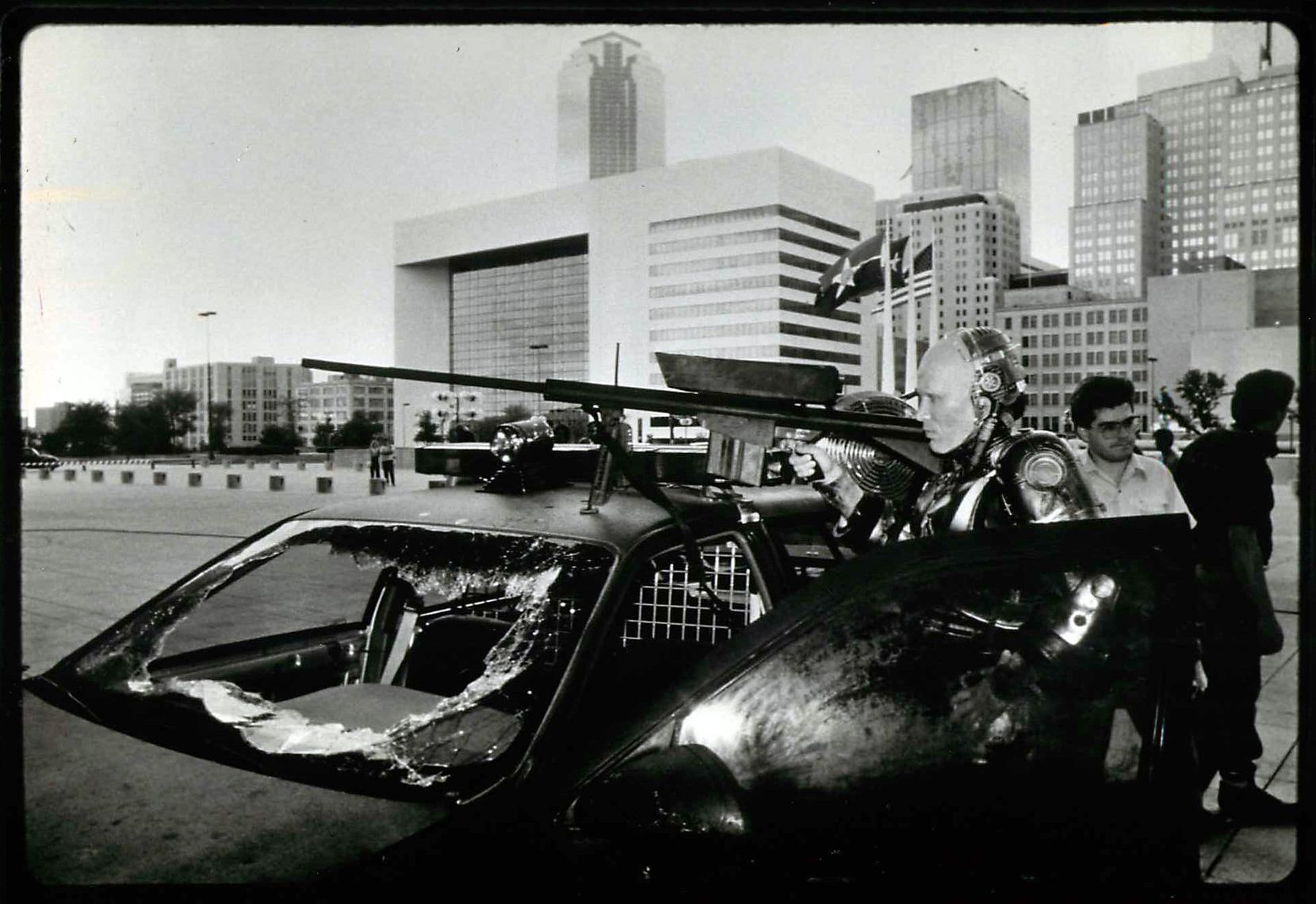 The Dallas skyline looms behind actor Peter Weller during filming of the 1987 dystopian film 'RoboCop' outside Dallas City Hall.