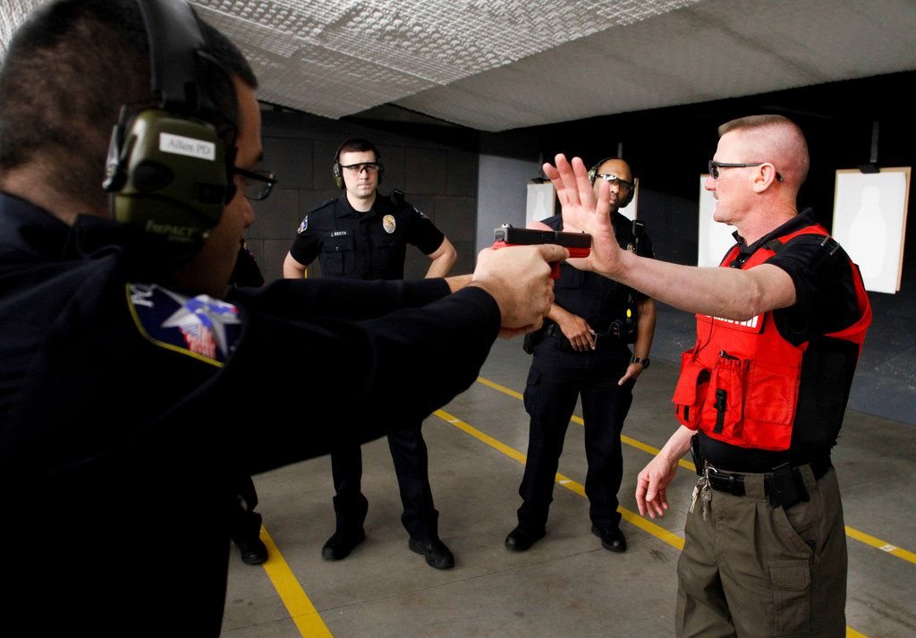 Ricky Pollan, range master of the Allen Police Department, uses a training pistol to show officers how the force of a handgun firing will affect an officer in the correct firing position.