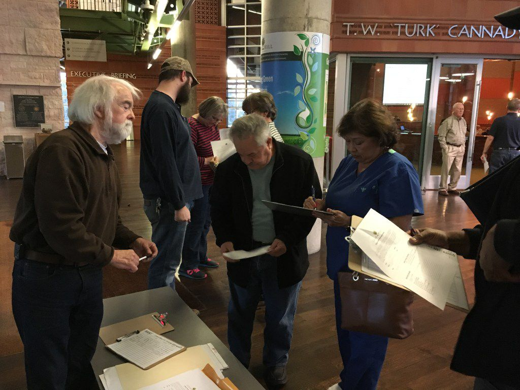 Cedar Hill resident Wes Pool hands out information before a City Council meeting to discuss the approval of a mixed-use development that would feature a mix of retail and multi-family apartment units. Pool and dozens of others spoke out against the development, which was eventually approved.