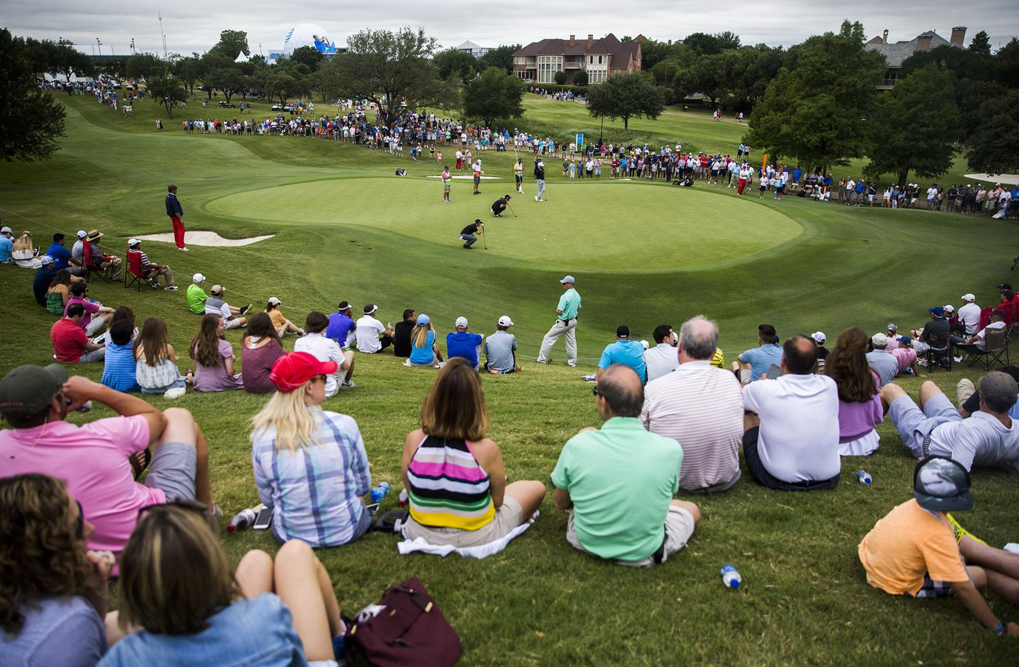 Spectators watch as Dustin Johnson, Cameron Tringale and Bud Cauley line up their putts on the first green during round three of the AT&T Byron Nelson on Saturday, May 20, 2017 at TPC Four Seasons in Irving, Texas.