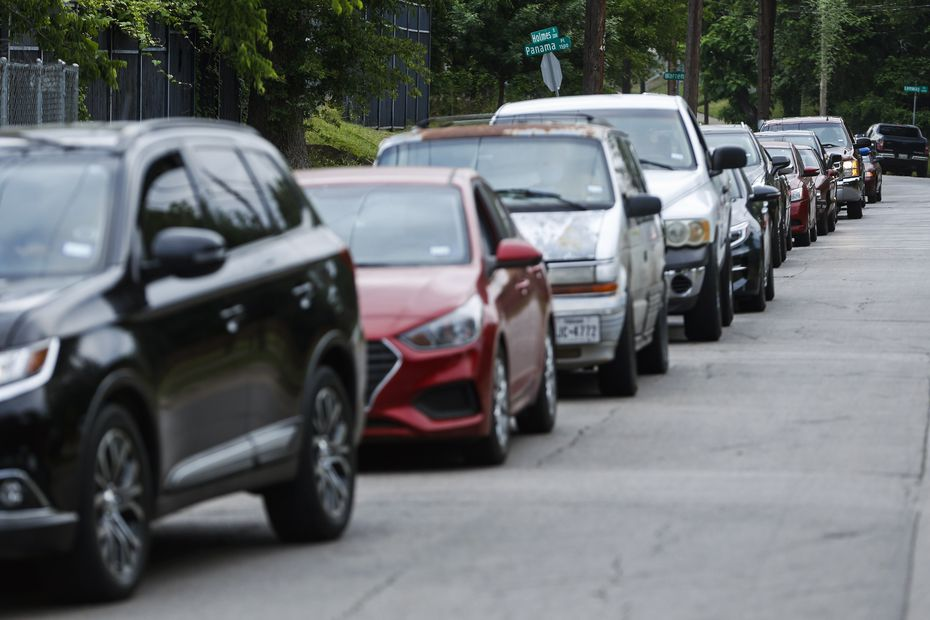 Cars line up along Holmes Street as they await entry to pick up groceries at the St. Philip's food pantry.