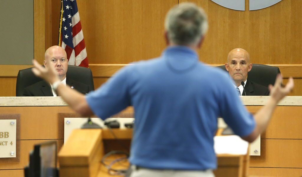 Commissioner Chris Hill (left) and County Judge Keith Self (right) listened to a speaker during an August hearing.