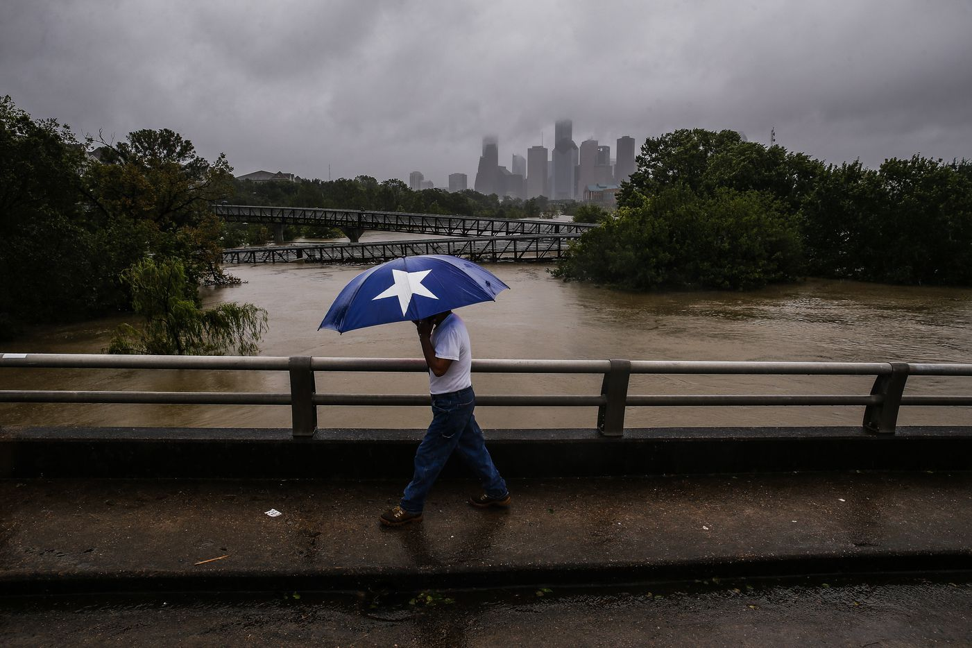 Armando Bustamante walks along the street over Buffalo Bayou as flood waters from Tropical Storm Harvey flow toward downtown Houston Tuesday, Aug. 29, 2017.  More than 17,000 people are seeking refuge in Texas shelters, the American Red Cross said. With rescues continuing, that number seemed certain to grow.
