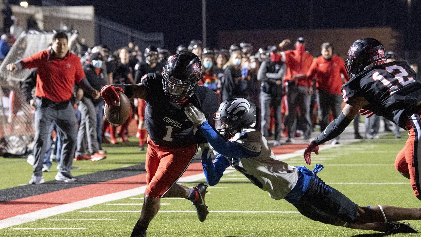 Coppell senior wide receiver KJ Liggins (1) fights through the tackle of Plano West senior linebacker Arwin Sino (6) to score the go-ahead touchdown in the fourth quarter of a high school football game on Friday, October 30, 2020 at Buddy Echols Field in Coppell, Texas. Coppell won 31-20.