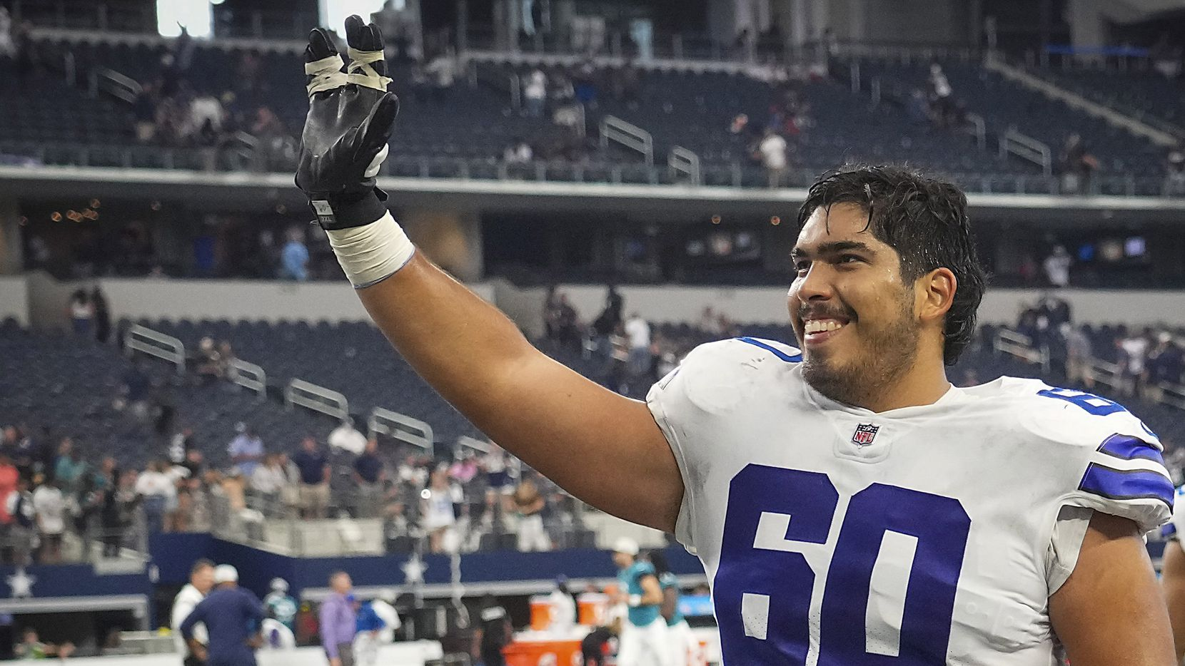 Dallas Cowboys offensive tackle Isaac Alarcon waves to the crowd as he leaves the field following a loss to the Jacksonville Jaguars in a preseason NFL football game at AT&T Stadium on Sunday, Aug. 29, 2021, in Arlington.