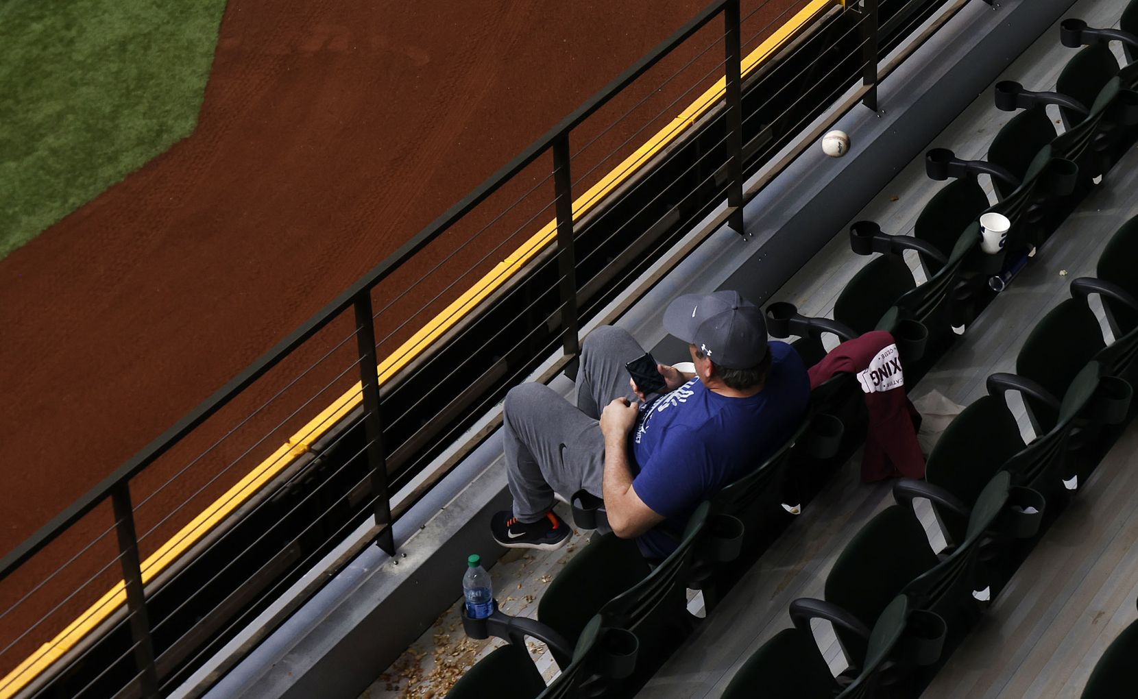 A home run ball off the bat of Texas Rangers batter Andy Ibáñez nearly hits a fan sitting in right field at Globe Life Field in Arlington, Texas. The Rangers were playing the Milwaukee Brewers in an exhibition game, Tuesday, March 30, 2021. (Tom Fox/The Dallas Morning News)