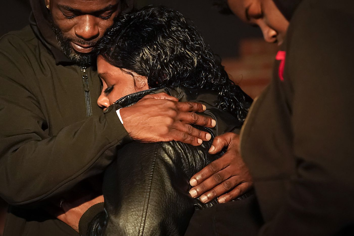 """Monique Mitchell is consoled during a vigil for her son Marc """"Flea"""" Strickland, an 18-year-old victim of a shooting at Dallas ISD basketball game, at Bushman Park on Sunday, Jan. 19, 2020."""
