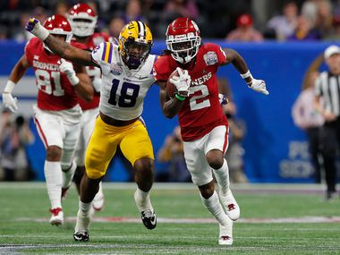 FILE - Oklahoma wide receiver CeeDee Lamb (2) gains yards as LSU's K'Lavon Chaisson (18) gives chase during the Peach Bowl at Mercedes-Benz Stadium on Dec. 28, 2019, in Atlanta. (Photo by Kevin C. Cox/Getty Images)