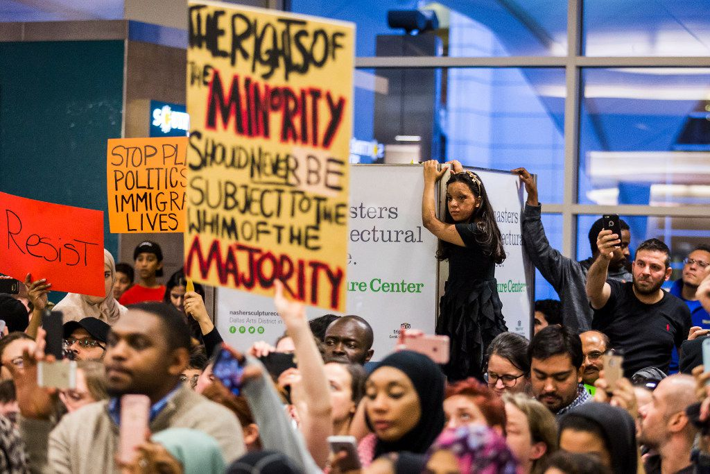 Protestors listen as organizers announce an end to the demonstration at DFW International Airport on Sunday, Jan. 29, 2017.