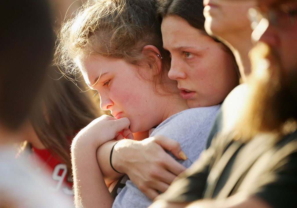 Mourners embrace during the vigil  in Santa Fe, Texas Friday. A substitute teacher and a Pakistani exchange student are among the first confirmed victims. The injured include a school resource officer and a sophomore baseball player.
