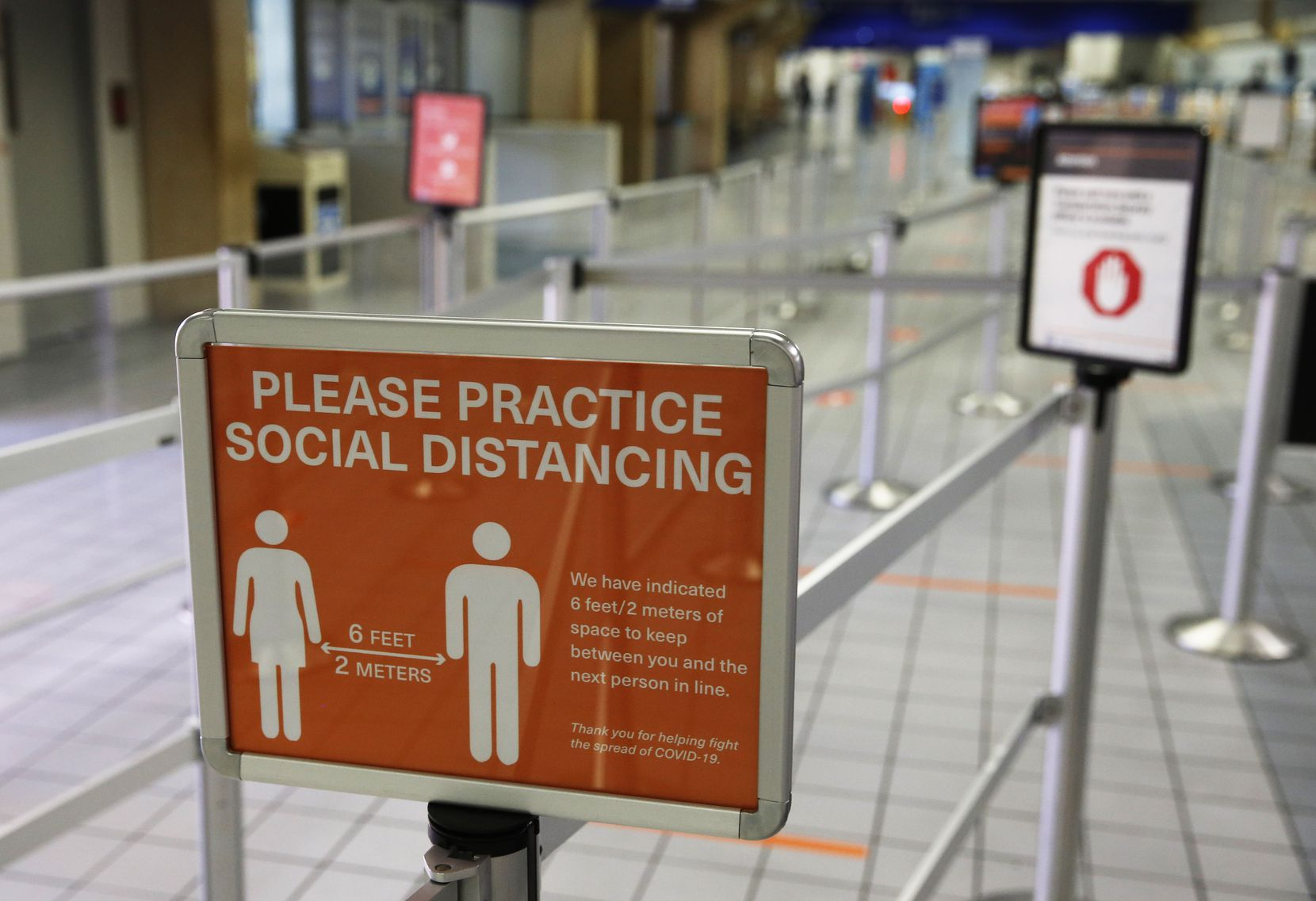 A sign reminds people to practice social distancing in the security checkpoint line at DFW International Airport on Wednesday, April 8, 2020.