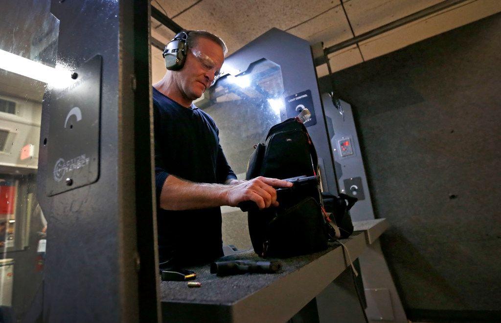 NRA TV anchor and reporter Grant Stinchfield checks his handgun after firing at DFW Gun Range in Dallas.